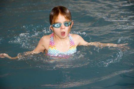 Child in a swimming pool learning to swim Stock Photo