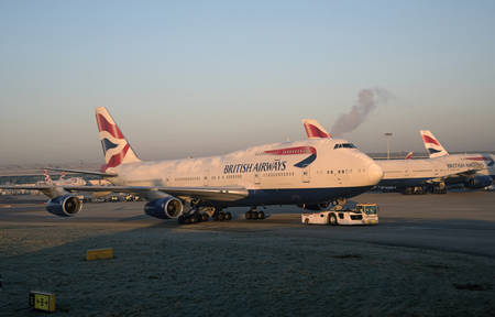 towed: Passenger jet being towed by a tractor at London Airport UK Editorial