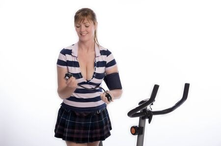 age forty: Woman checking blood pressure after using exercise bike