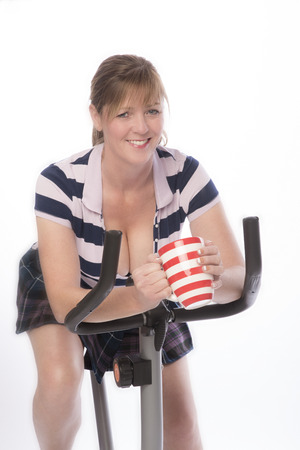 taking a break: Woman with mug of tea taking a break from the exercise bike Stock Photo