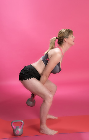 knees bent: Woman with bent knees using a kettle bell to exercise
