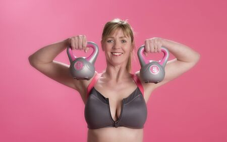 kettle bell: Woman using kettle bell weights to exercise Stock Photo