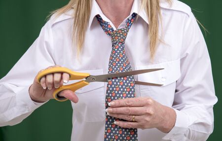 snipping: Woman using scissors to cut a necktie in half for a joke