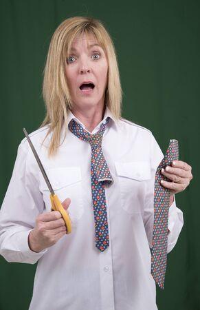 snip: Woman using scissors to cut a necktie in half for a joke