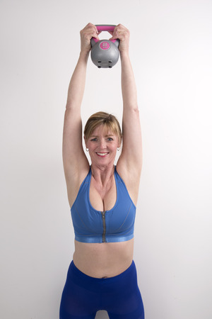 kettle bell: Woman using a 2 kg weight kettle bell to exercise