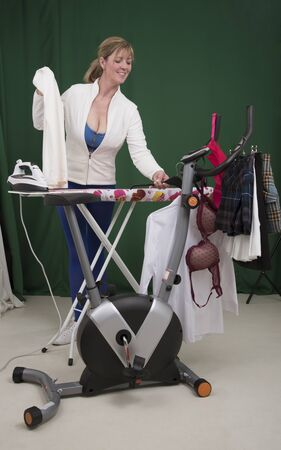 woman ironing: Woman ironing clothes using exercise bike as a clothes horse Stock Photo
