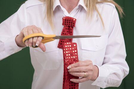 snip: Woman having fun cutting a red necktie in half