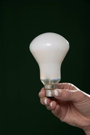 womans: Womans hand holding an household lightbulb Stock Photo