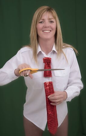 snipping: Woman having fun cutting a red necktie in half