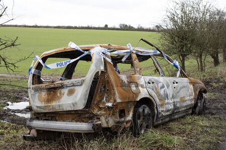 burnt out: Burned out car and police tape in open countryside