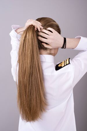 naval: Woman naval officer restyling her hair to fit inside her cap