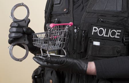 female hand: Police officer holding handcuffs and supermarket trolley in concept of shoplifting