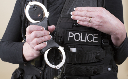 rigid: Female police office holding a pair of rigid handcuffs