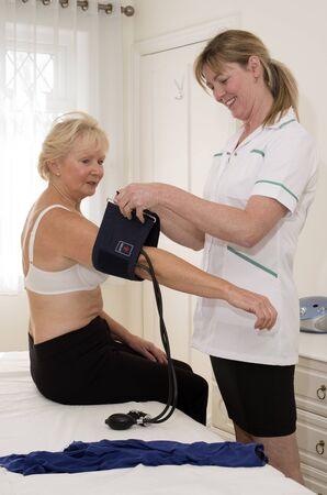 pacientes: Enfermera que controla la presi�n arterial de un paciente Foto de archivo