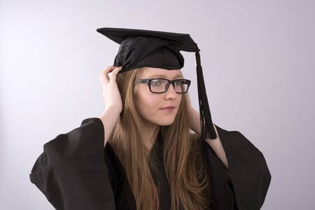toga y birrete: Retrato de un estudiante universitario que ajusta su casquillo de la graduación Foto de archivo