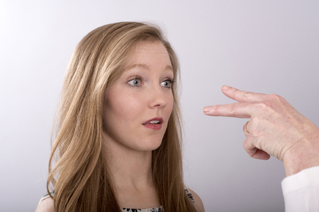 gesticulate: A two fingure gesture towards a young womans eyes