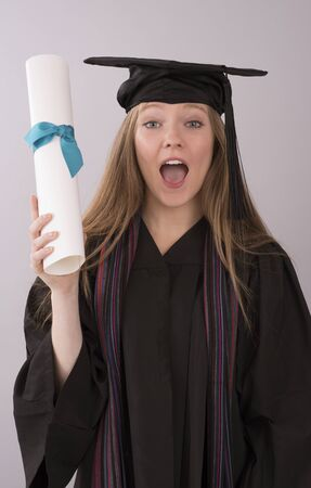 sucessful: Young graduate in cap and gown with diploma