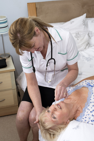nursing staff: Nurse administering nasal drops into a patients nose Stock Photo