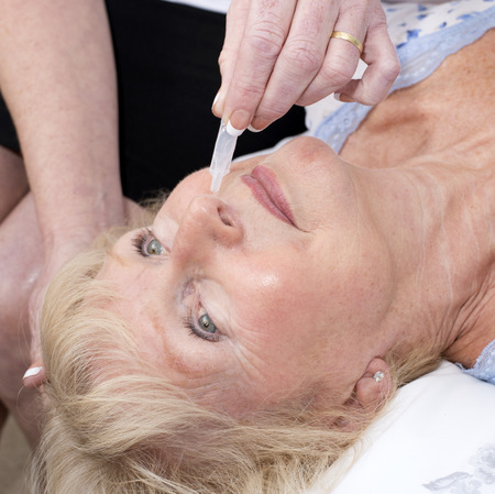 Nurse administering nasal drops into a patients nose Stock Photo