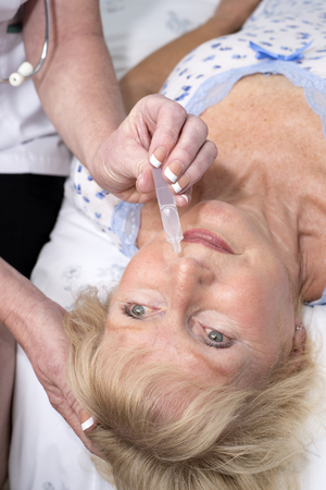 nasal: Nurse administering nasal drops into a patients nose Stock Photo