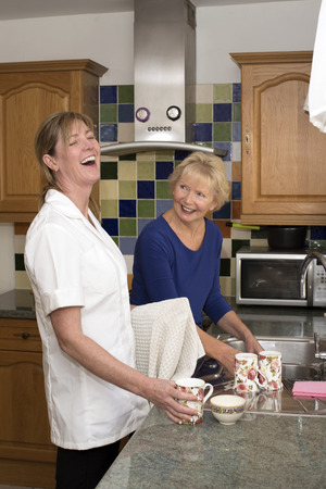 A carer who is laughing working with a client also laughing in the client's kitchen