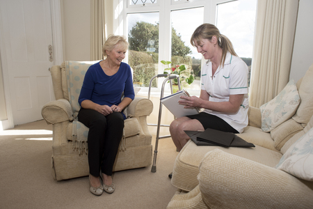 home visit: Nurse on a home visit talking with an elderly female patient