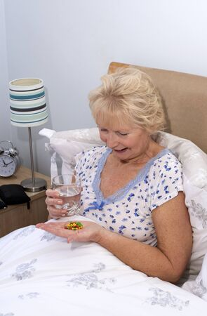 pill popping: Elderly woman taking tablets at bedtime Stock Photo