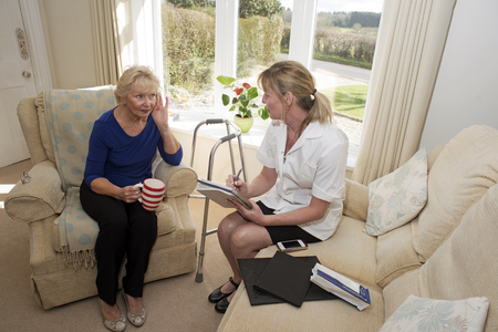 deafness: Doctor on a home visit giving advice to a woman suffering from deafness