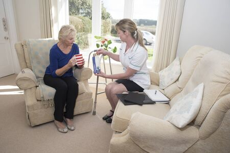 home visit: Health visitor with a patient on a home visit giving advice on prescription drugs