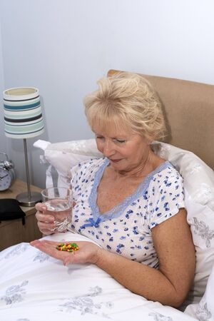 bedtime: Elderly woman taking tablets at bedtime Stock Photo