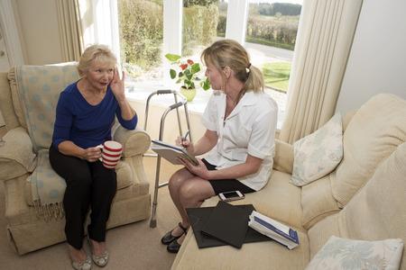 visitador medico: M�dico de una visita al hogar dando consejos a una mujer que sufre de sordera Foto de archivo