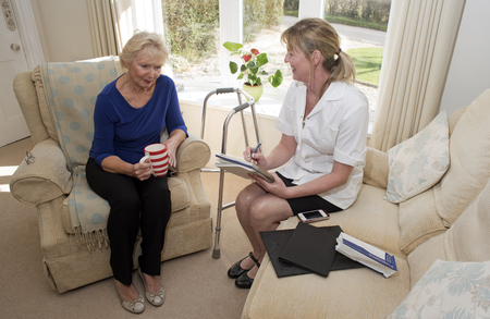 home visit: Nurse on a home visit with an elderly patient