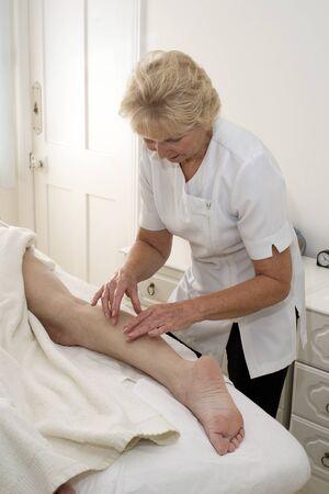 masseuse: A masseuse massaging a clients leg Stock Photo