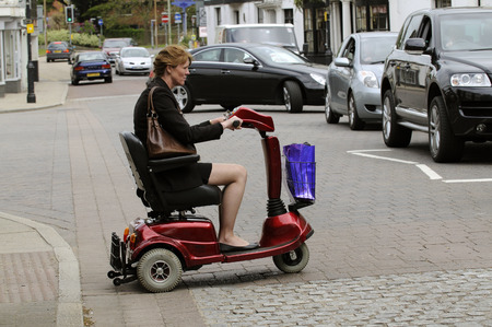 rascal: Woman seated on a mobility scooter crosses the road at a pedestrian crossing