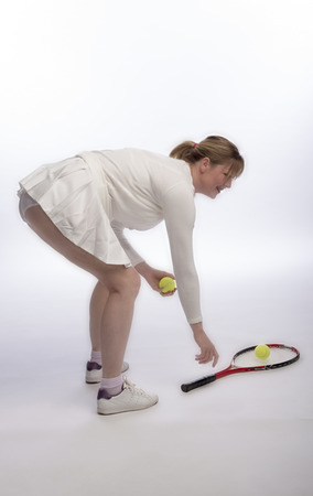 Woman tennis player bending to pick up racquet Stock Photo
