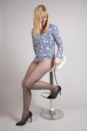 Blond woman in dark coloured tights putting on high heel shoes