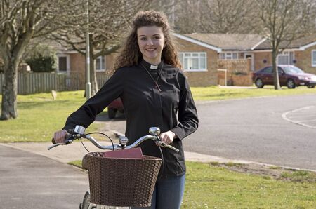 vicar: Young attractive parish priest using a bicycle as transport