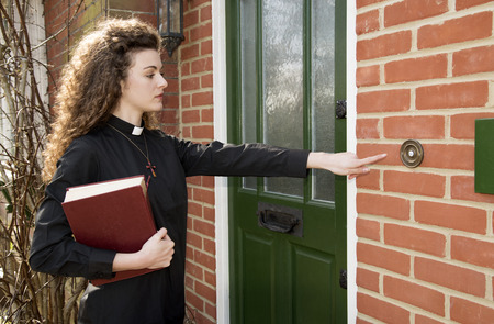 cleric: Young woman priest ringing door bell of a house Stock Photo