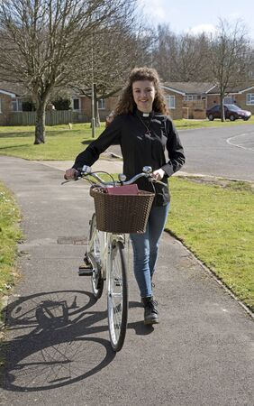 theological: Young attractive parish priest using a bicycle as transport