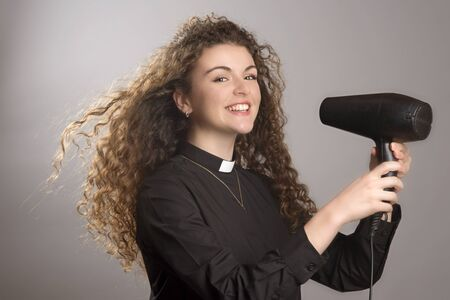 devout: Woman priest with long hair using a hair dryer