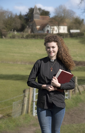 vicar: Young vicar walking around her country parish