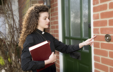 house call: Young woman curate ringing door bell of a house