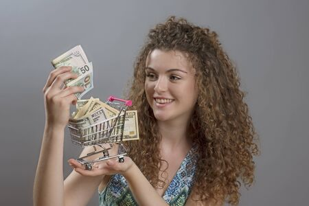 minature: Concept of the cost of living a smiling woman holding supermarket trolley full of cash