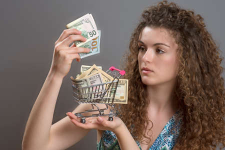 minature: Concept of the cost of living a woman with serious expression holding supermarket trolley full of cash Stock Photo