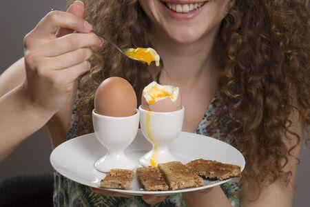 Young girl eating boiled eggs for breakfast Standard-Bild
