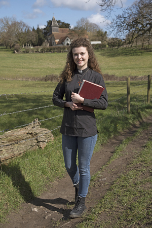 Young parish priest walking in her countryside parish