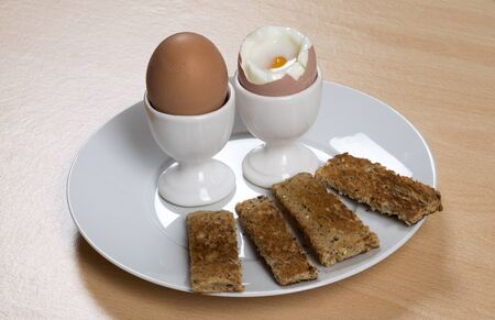 boiled eggs: Breakfast of boiled eggs and soldiers on a plate Stock Photo