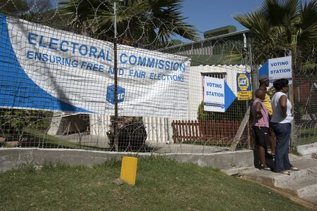 southern africa: IMIZAMO YETHU TOWNSHIP WESTERN CAPE SOUTH AFRICA - APRIL 2016 - Voting station with woman standing outside in this township in Hout Bay Western Cape Southern Africa