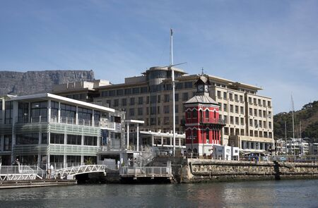 va: CAPE TOWN SOUTH AFRICA - APRIL 2016 - The V&A Waterfronts clocktower, Mandela Gateway building and Nedbank offices overlooked by Table Mountain