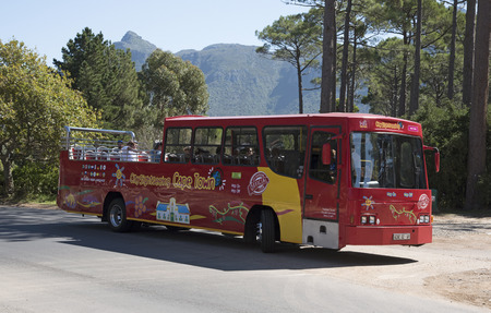 tourists stop: CONSTANTANIA WESTERN CAPE SOUTH AFRICA - APRIL 2016 - A red single deck tour bus and passengers visiting the Constantia region of the Western Cape Southern Africa